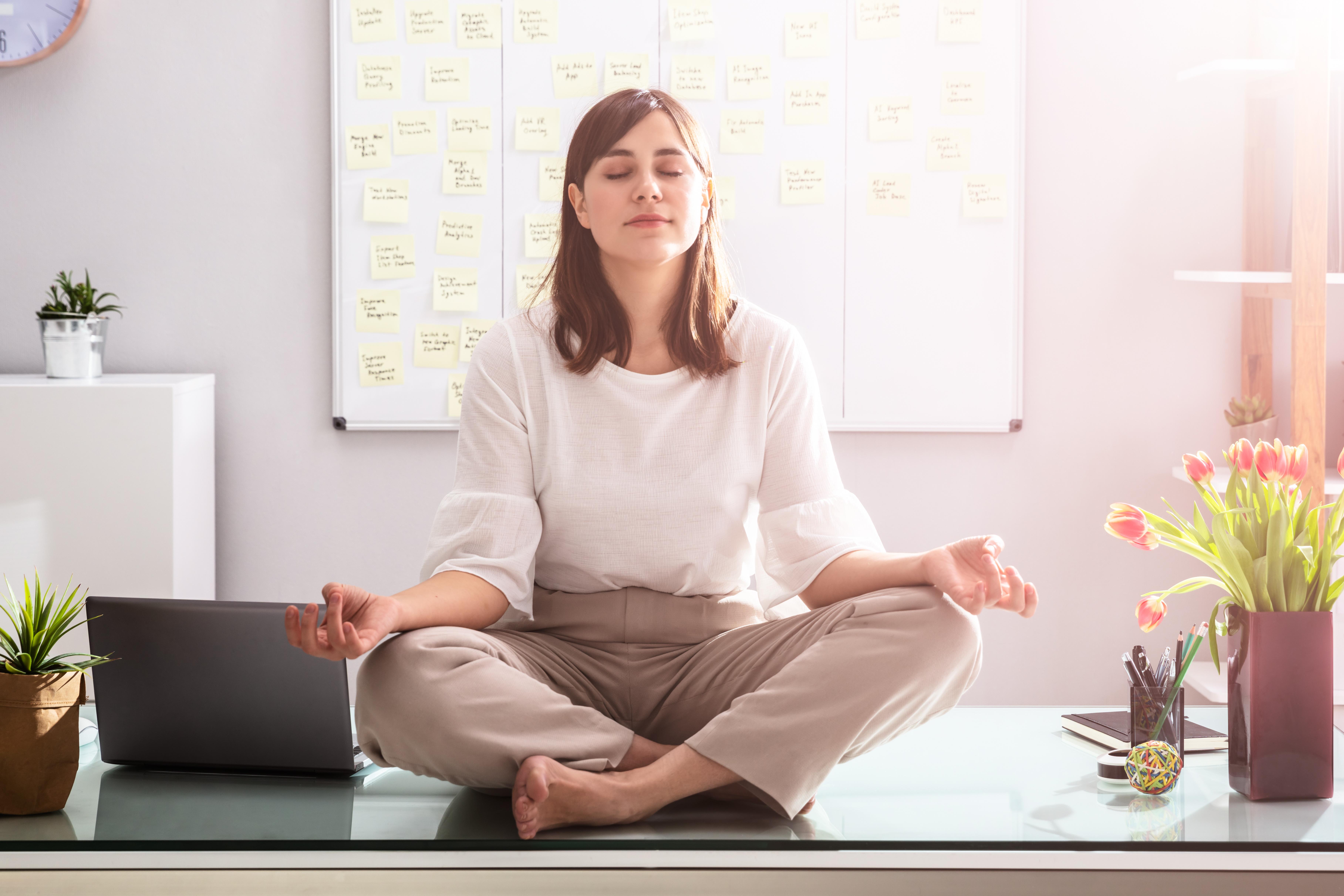 woman meditating of desk